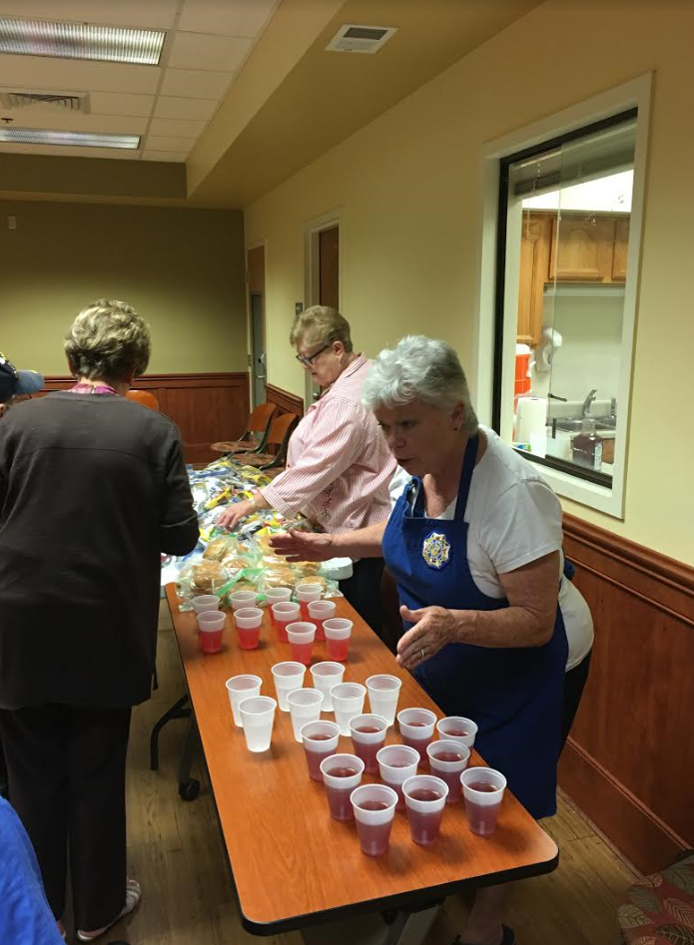 Auxiliary President Carolyn Hurd and Pam Koberg pass out refreshments at the bingo event.